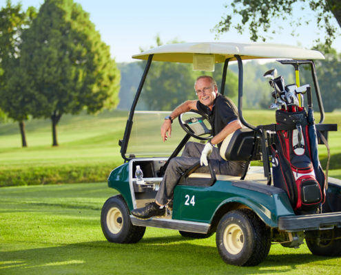 Mature man sitting in a golfcart on the green