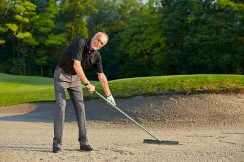 Senior golfer rake the bunker
